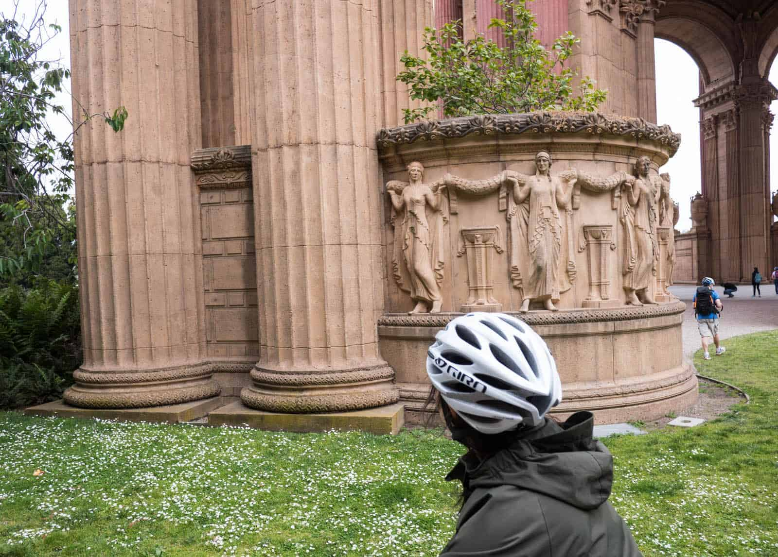 San Francisco's Palace of Fine Arts relief detail. Woman riding past on a bike.